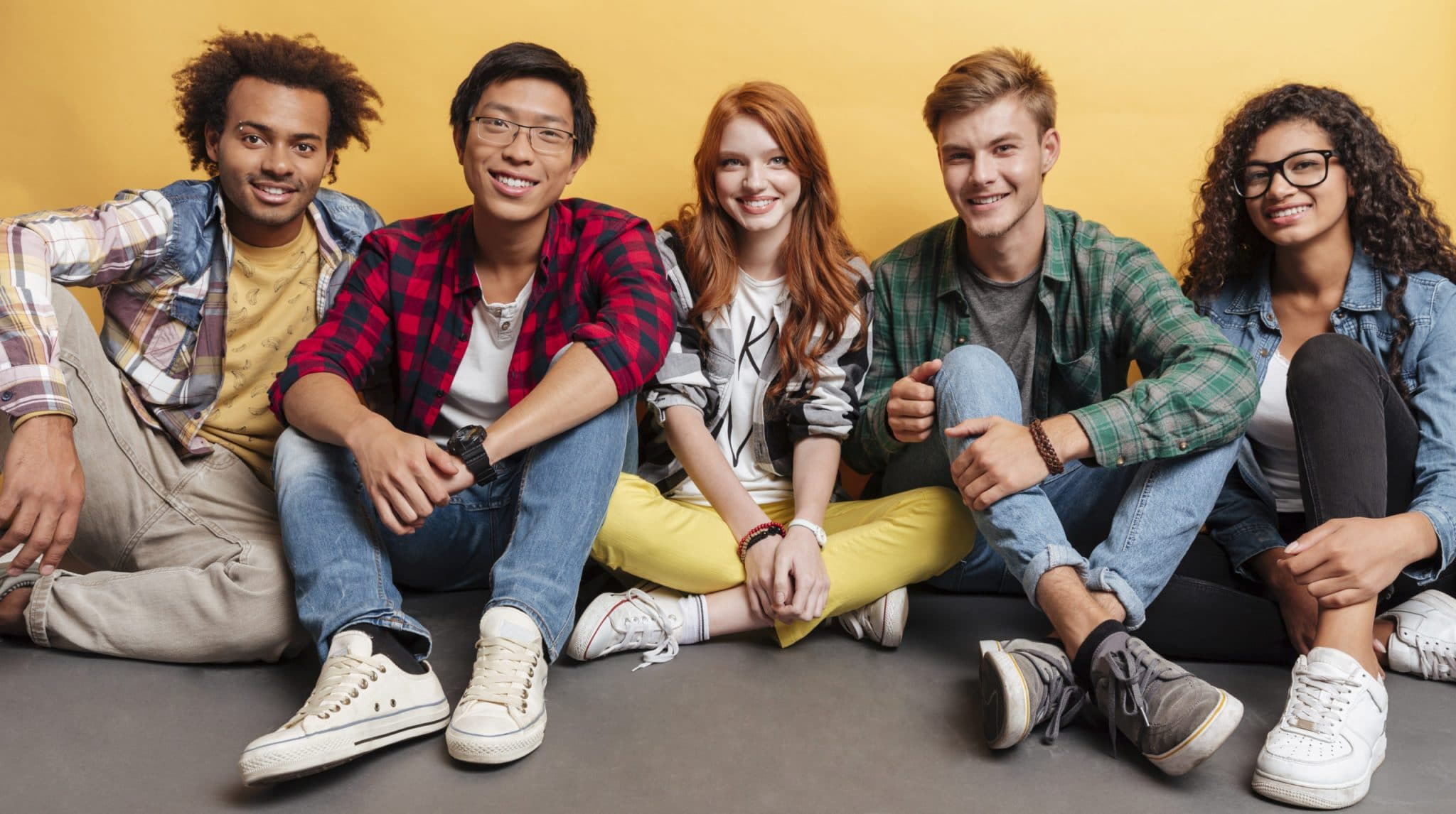 Multiethnic group of smiling friends sitting on the floor together