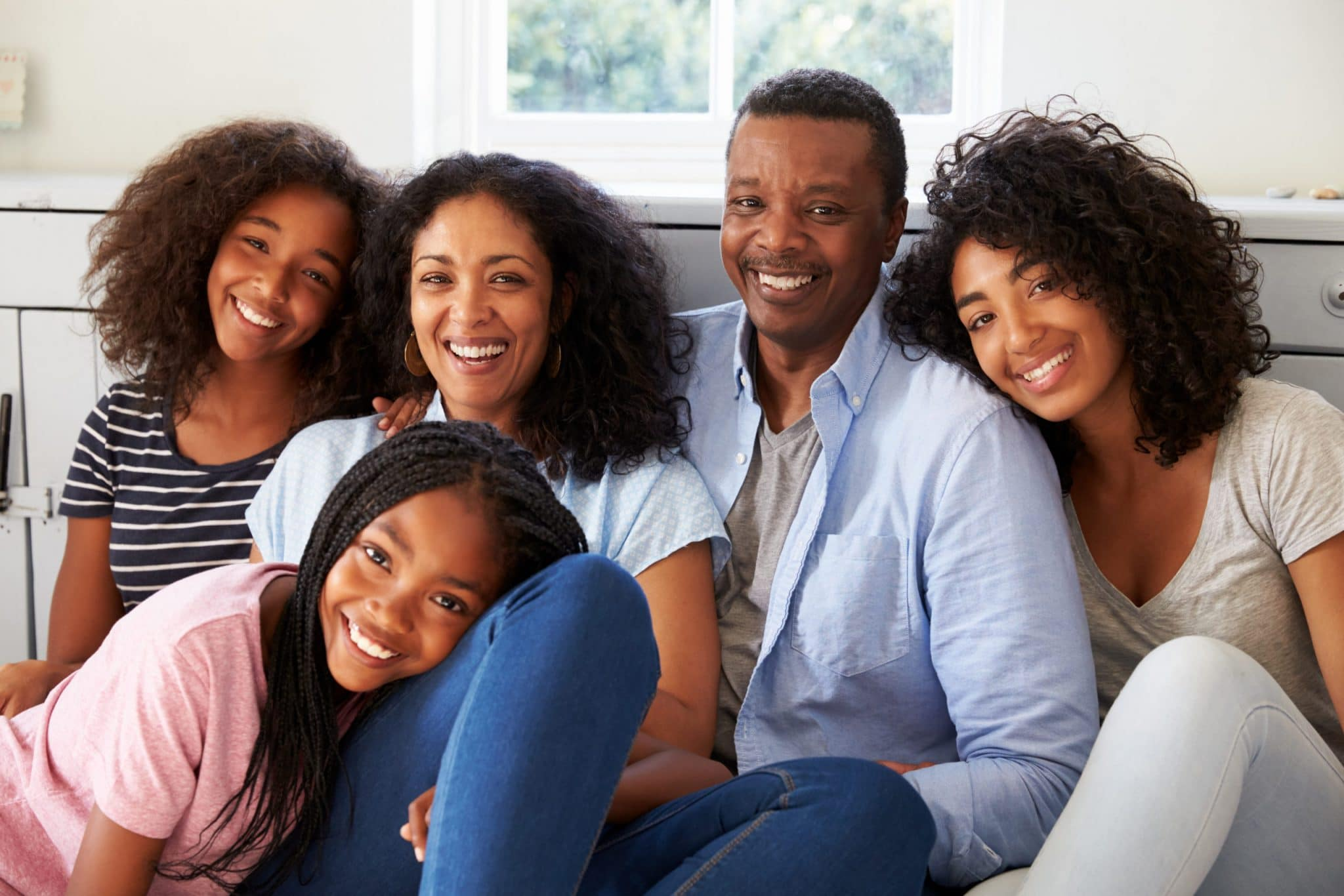 Portrait Of Smiling Ethnic Family Relaxing On Seat At Home