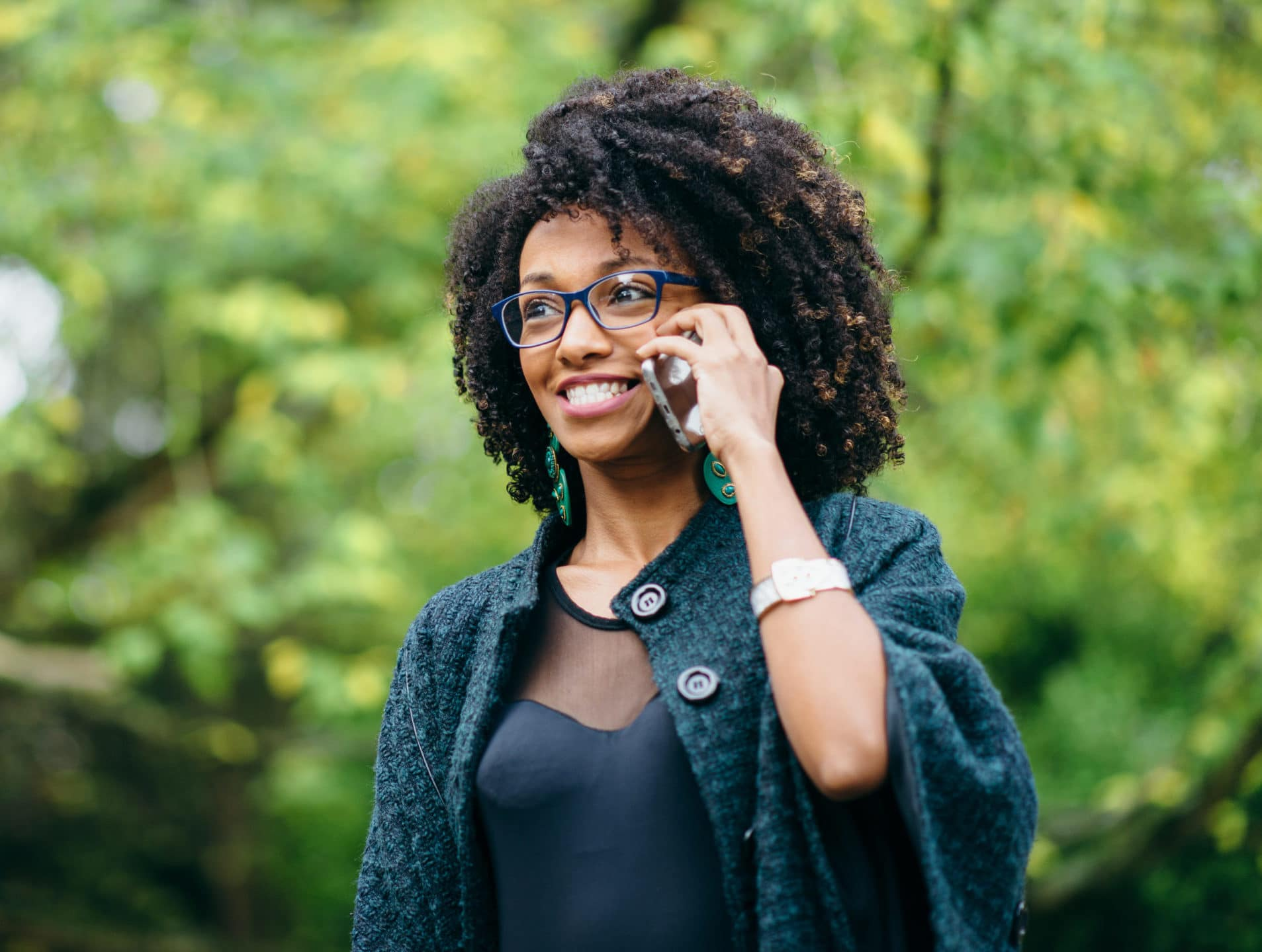 Happy black woman standing outside during a mobile phone call