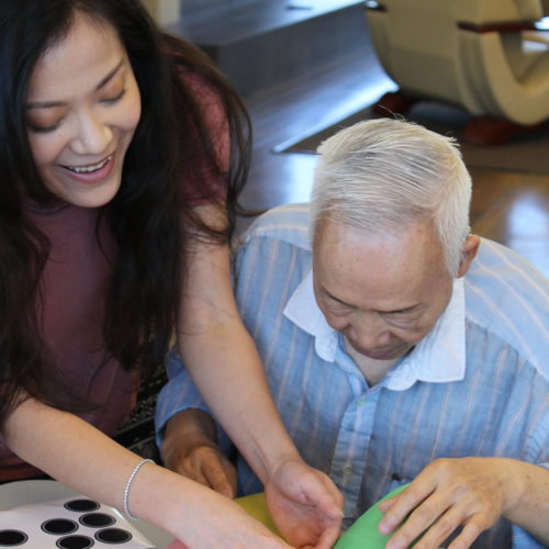 Asian Pacific Development Center adult education. A young asian woman and older asian man working on a craft project.