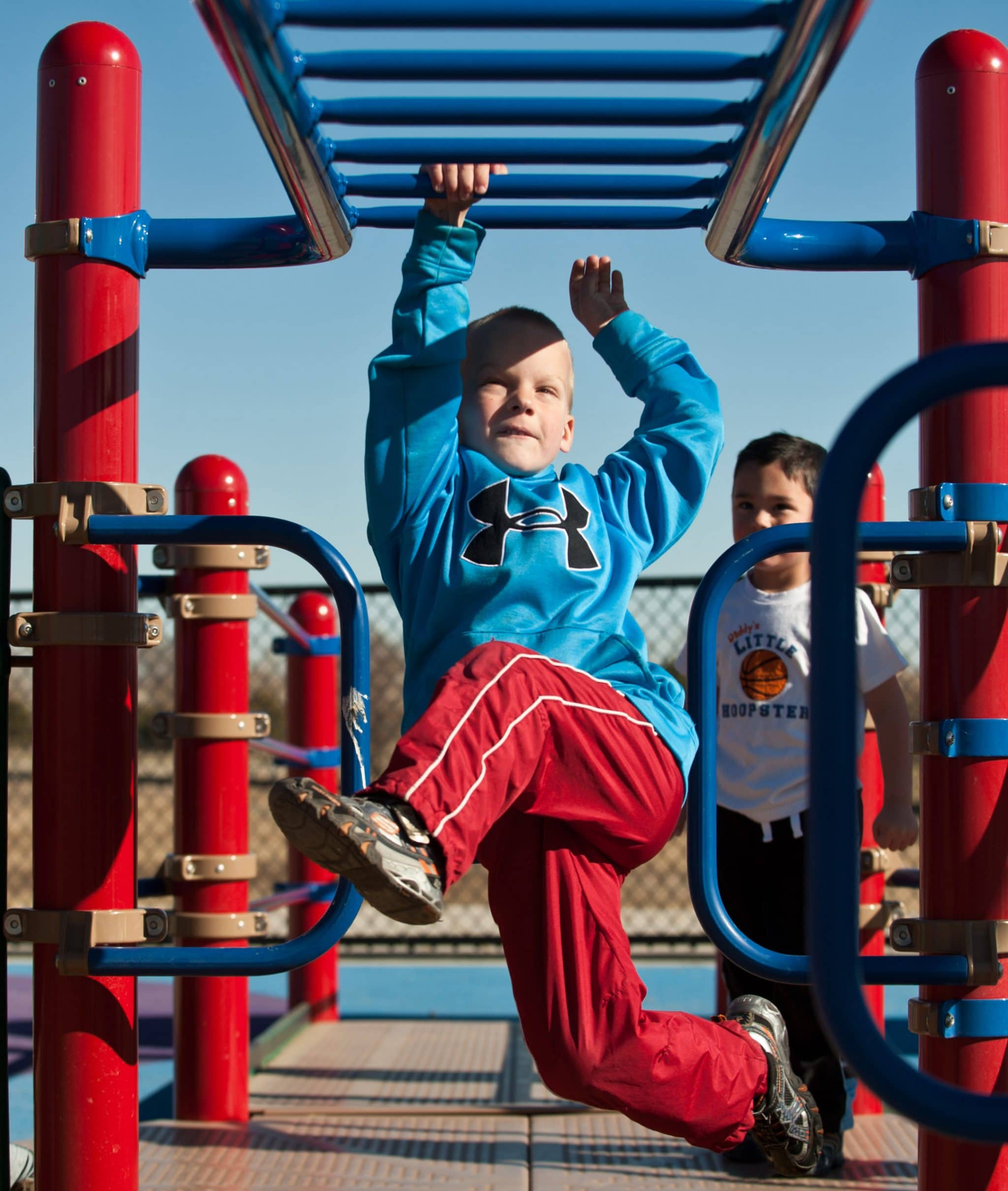 Blond caucasian boy hanging from the monkey bars at a playground