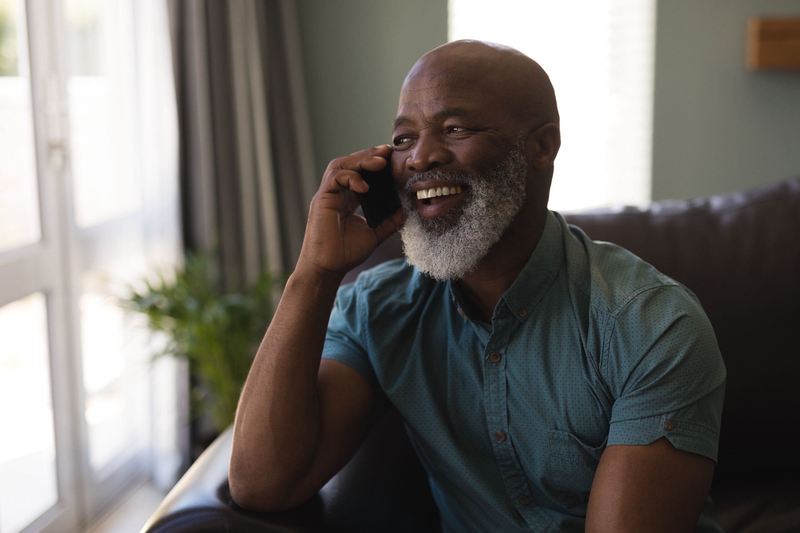 Older Afro-american man on cell phone talking and laughing.